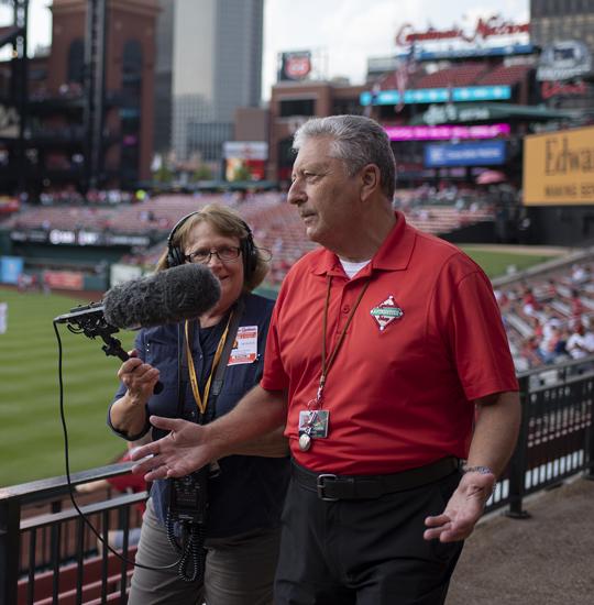 Man being interviewed in ballpark.