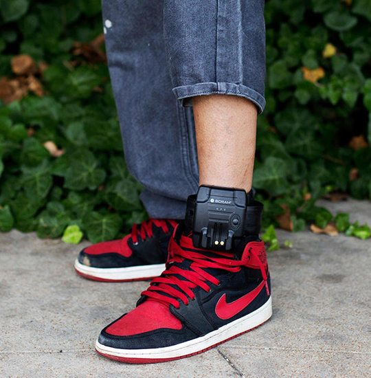 Lower legs with one pants leg pulled up to reveal an ankle monitor.
