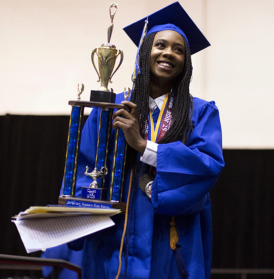Girl in graduation gown holding trophy.
