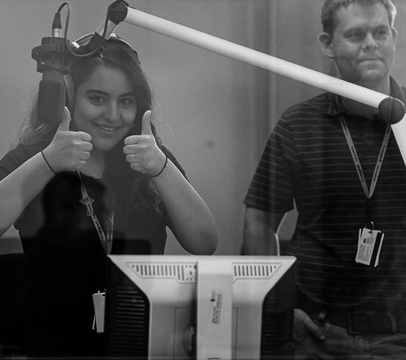 Girl in broadcast booth giving a thumbs up.