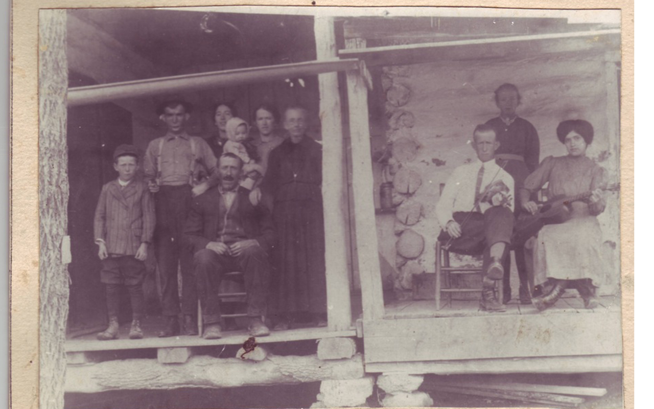 """Frank Vess Portell family. The woman with the guitar is Nellie Hopkins Portell. She is wearing button shoes and has the Gibson Girl hairstyle. The man with the fiddle is Francis """"Brazz"""" Politte. His descendants are known as the Brazz Polittes."""